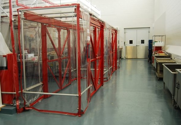 Inside of the pilot plant showing a row of plastic enclosed scaffolding structures.