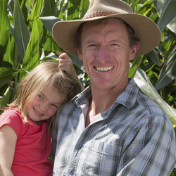 Man holding his daughter in his arms, in front of a corn field.