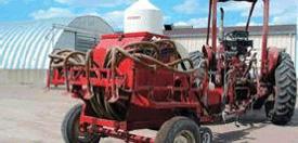 Un tracteur tire un épandeur d'herbicide.