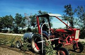 Un petit tracteur fait passer un pulvérisateur à rampe en U sur de jeunes arbres.