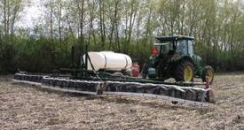 Un tracteur tire un pulvérisateur d'herbicide dans un champ.