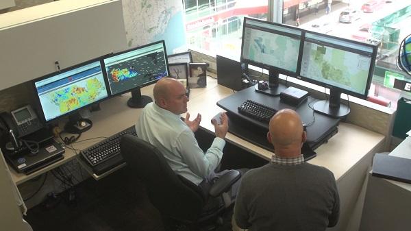 Deux hommes sont assis à un bureau en forme de L avec quatre écrans d'ordinateur affichant diverses cartes des Systèmes d'information géographique avec des données d'exploitation.