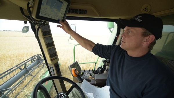 A man gestures to a small computer screen in the top left of the cab of a combine harvester.