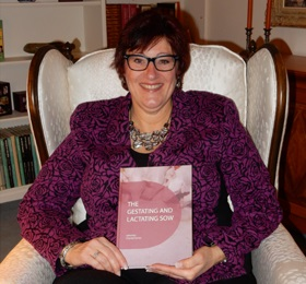 Photo of research scientist Chantal Farmer holding a copy of her book The Gestating and Lactating Sow.