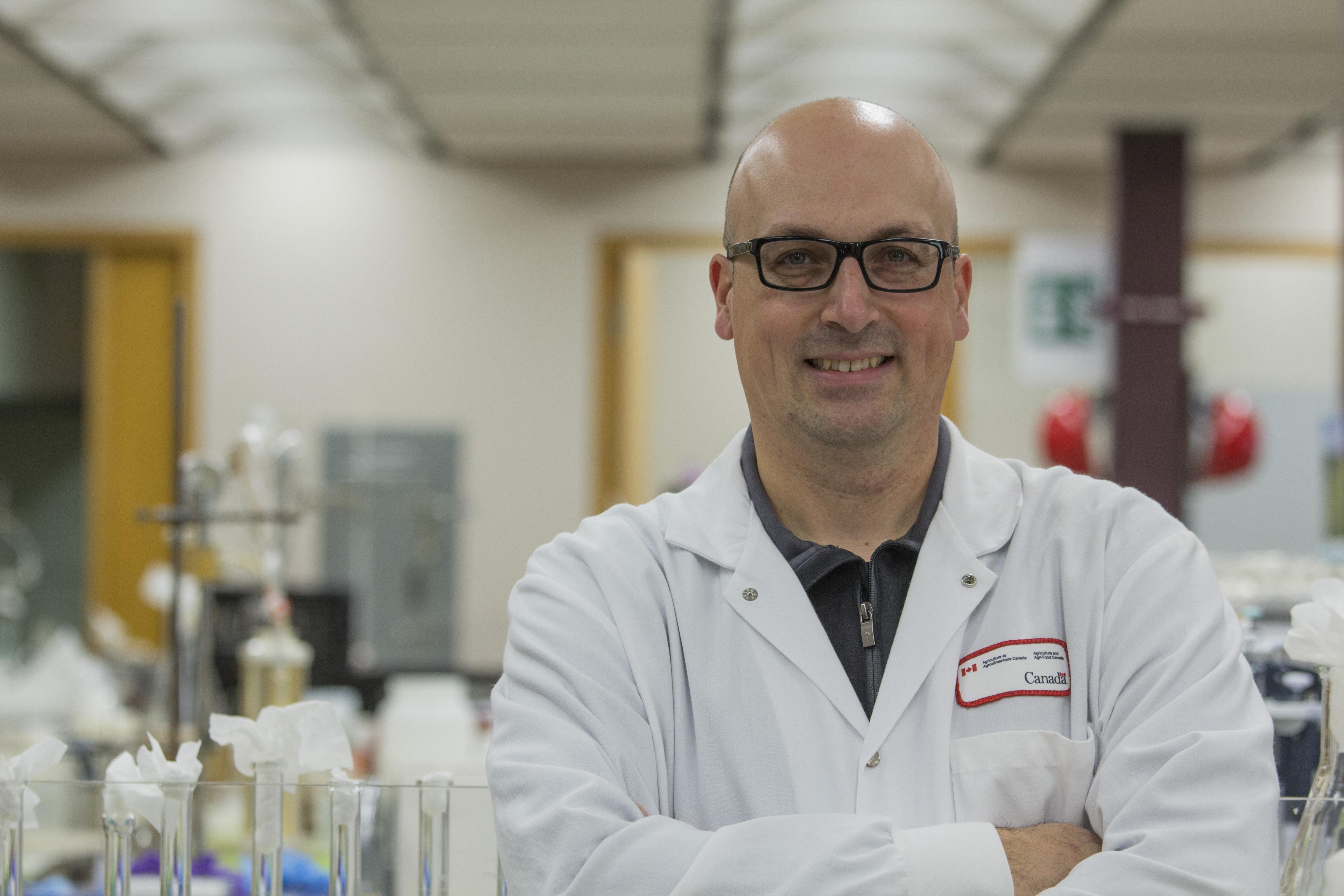 Le chercheur  et chef de projet Sébastien Villeneuve vêtu d'un sarrau blanc dans un laboratoire.
