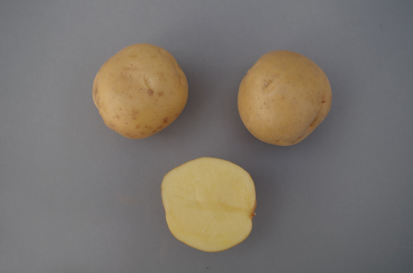 Two whole potatoes and one potato cut in half.