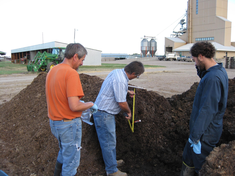 Trois chercheurs examinent le compost à l'extérieur.