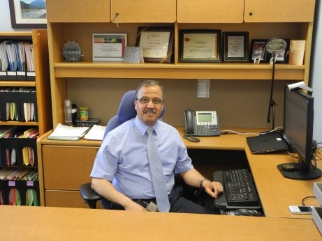 Dr. Elsayed Abdelaal sits at his desk with certificates and awards on the shelf behind him.