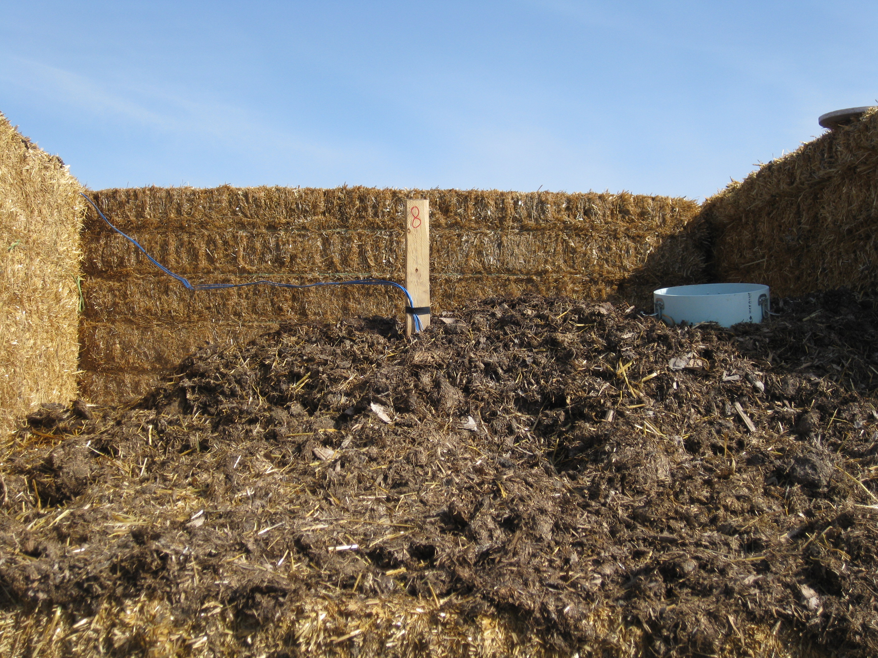 Large straw bales of hay acting as barrier to manure.