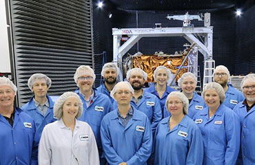 A group of 13 people in blue lab coats stand smiling in front of one of the RCM spacecraft in a warehouse.