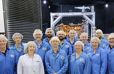 Groupe de 13 personnes en sarraus bleus, souriant, debout, devant l'un des engins spatiaux de la mission de la Constellation RADARSAT dans un entrepôt.