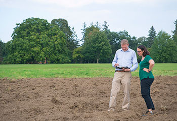 On the right of the photo, Dr. Andrew Davidson and Dr. Catherine Champagne look down at a computer tablet in his hands while standing in a plowed field with trees in the background.