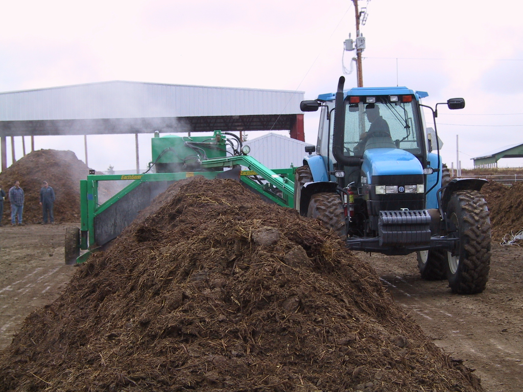 A blue tractor turning over manure.