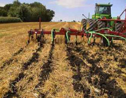 Photo shows a field being seeded using an air-seeder with a minimum of soil disturbance.