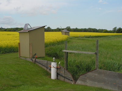 Two monitoring equipment huts and v-notch weirs to channel runoff. There is a field of canola in the background.
