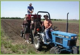 Des fermiers avec un tracteur qui remorque le matériel d'ensemencement habituel.