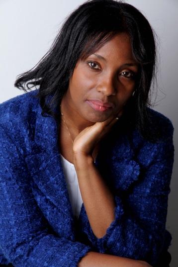 Portrait photo of Dr. Joyce Boye, sitting, wearing a blue jacket and white shirt.