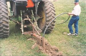 um fazendeiro instalando um sistema de pipeline .
